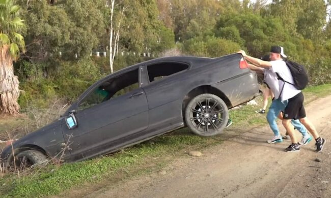 Блогер толкает авто в реку, фото: скриншот YouTube